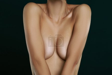 naked  woman covering her breast with hands