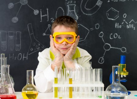 schoolboy gown and gloves watching chemical experiment in tube