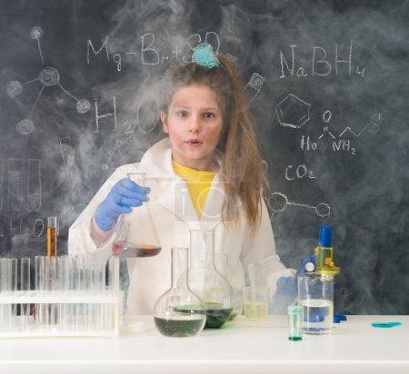 Photo pour Excitée écolière en fumée après expérience chimique dans le laboratoire scool - image libre de droit