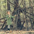 Little girl in the wood near  hut. Photo in retro ...