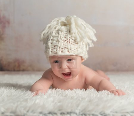 Photo pour Drôle petit bébé dans grand chapeau rampant sur couverture de laine - image libre de droit