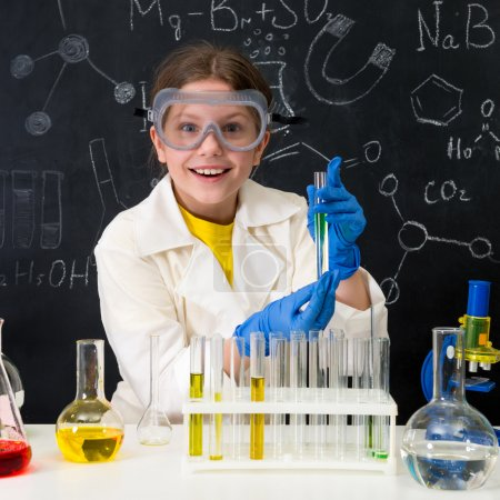 Photo for Schoolgirl in white gown doing experiments with liquids in chemistry lab - Royalty Free Image