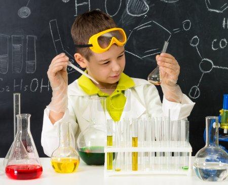 Photo pour Robe d'écolier et gants regarder l'expérience chimique dans le tube dans le laboratoire de chimie - image libre de droit