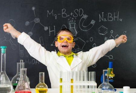 Photo pour Écolier excité avec les mains en l'air dans le laboratoire de chimie a fait une découverte - image libre de droit