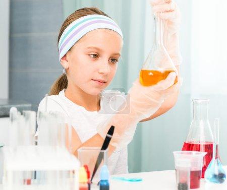 Photo pour Mignonne petite fille avec des flacons pour la chimie - image libre de droit