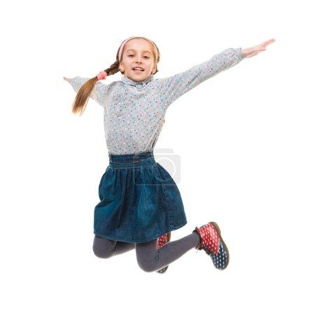 photo of joyful little girl jumping