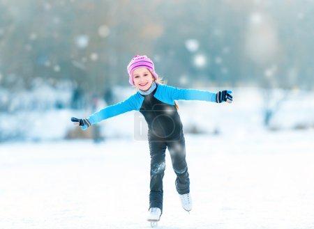 Photo pour Jolie petite fille gaie en costumes thermiques patiner en plein air - image libre de droit