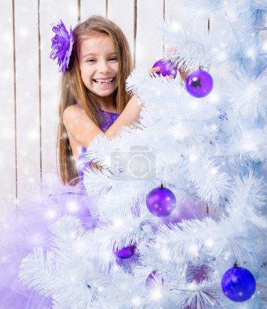 Photo pour Petite fille souriante dans une robe lilas décorée boules violettes sapin de Noël blanc - image libre de droit