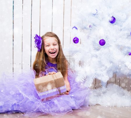 Photo pour Petite fille souriante avec un cadeau dans les mains près de l'arbre de Noël blanc - image libre de droit
