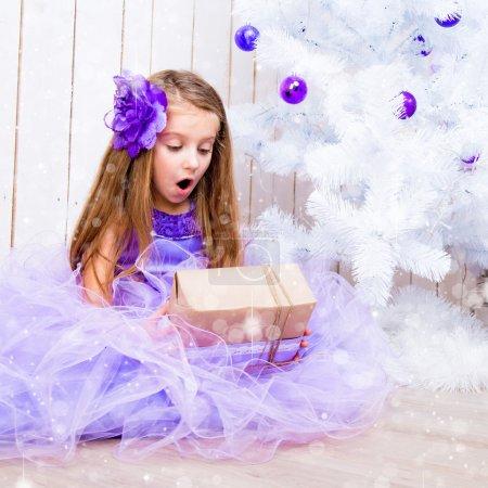 Photo pour Petite fille surprise avec un cadeau dans les mains près de l'arbre de Noël blanc - image libre de droit