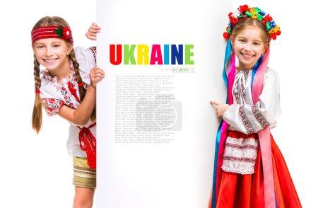 Photo pour Deux petites filles dans le costume national ukrainien debout derrière le tableau blanc avec de l'espace pour le texte - image libre de droit