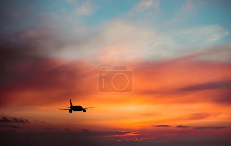 Airplane in  sky at sunset