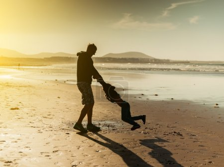Foto de Papá jugando con su hija en la playa al atardecer - Imagen libre de derechos