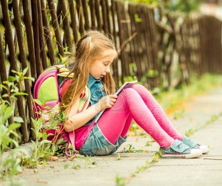 Schoolgirl reading  book  on  street