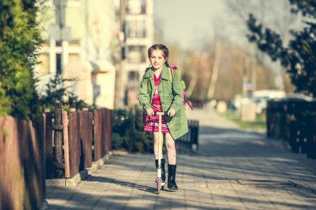 Photo pour Fille de retour de l'école sur un scooter - image libre de droit