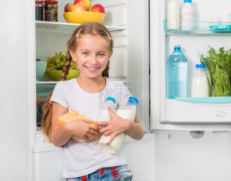 little girl holding cheese and milk