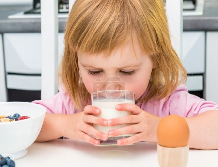 Photo for Little child drinking milk while breakfast - Royalty Free Image