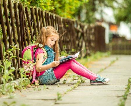 schoolgirl reading a book  on  street