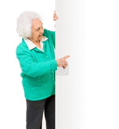 Photo pour Femme âgée aux côtés de panneau publicitaire sur fond blanc - image libre de droit