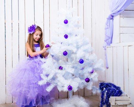 Photo pour Belle petite fille dans une robe lilas décoré blanc sapin de Noël boules violettes - image libre de droit