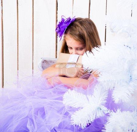 Photo pour Triste petite fille avec un cadeau dans les mains près de l'arbre de Noël - image libre de droit