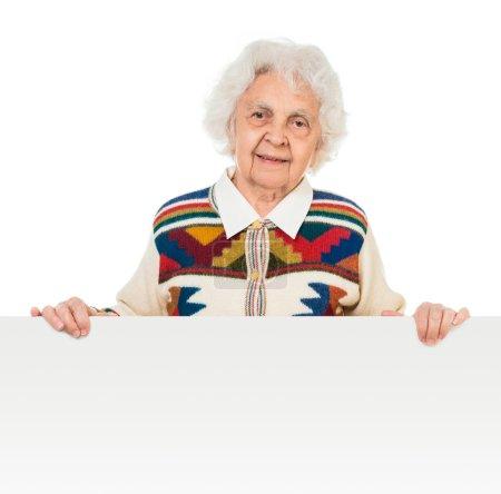 Photo pour Femme âgée derrière un panneau publicitaire sur fond blanc - image libre de droit
