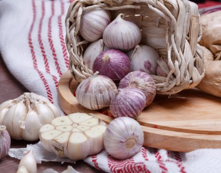 Garlic and pepper on a wooden table with utensils,...