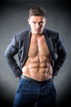 Photo for Handsome, muscular young man in jacket on a black background - Royalty Free Image