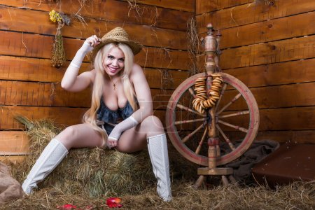 Photo for Young sexy girl in underwear and white boots sit in the barn with hay - Royalty Free Image