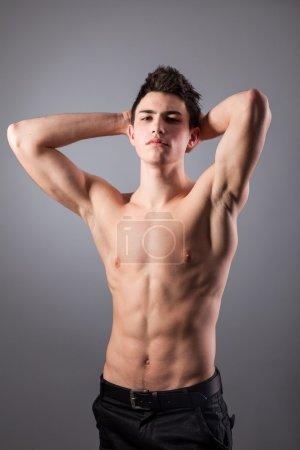 Portrait of young bodybuilder man on a black backg...