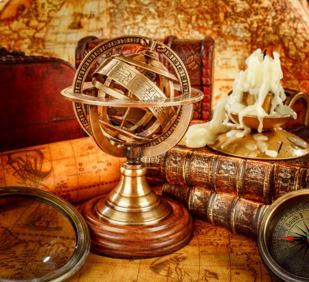 Vintage still life. Vintage old book and armillary sphere on an ancient world map in 1565.