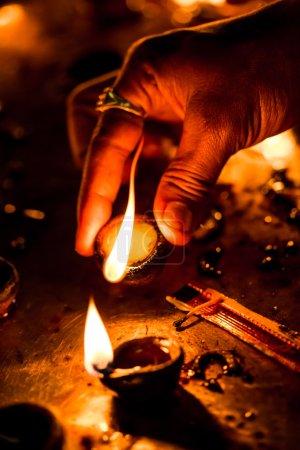 Photo pour Brûler des bougies dans le temple indien. Diwali la fête des lumières. Avertissement - prise de vue authentique avec iso élevé dans des conditions d'éclairage difficiles. Un peu de grain et des effets de mouvement flous . - image libre de droit