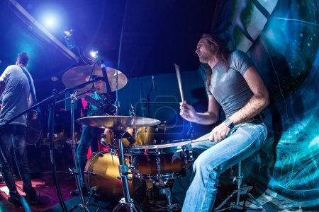 Foto de Baterista tocando el tambor en etapa. ADVERTENCIA - auténtico tiro con iso alto en condiciones de iluminación difíciles. Un poco de grano y efectos de movimiento borrosa. - Imagen libre de derechos