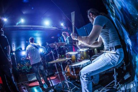 Foto de Baterista tocando el tambor en etapa. ADVERTENCIA - foco en el tambor, auténtico tiro con iso alto en condiciones de iluminación difíciles. Un poco de grano y efectos de movimiento borrosa. - Imagen libre de derechos