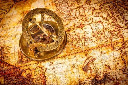 Photo pour Nature morte vintage. Vintage boussole se trouve sur une carte du monde antique en 1565 . - image libre de droit