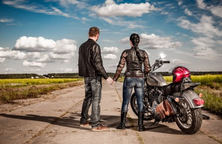 Biker man and girl stands on  road