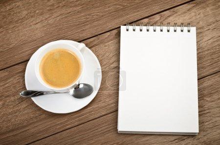 Photo pour Vue du dessus Coupe de café dans une tasse blanche et bloc-notes en spirale sur fond en bois - image libre de droit