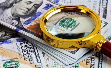 Photo for Investment analysis. Stack of US Dollar and magnifying glass - Royalty Free Image