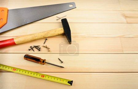 Photo pour Scie, vis, ruban à mesurer et marteau sur bois - image libre de droit
