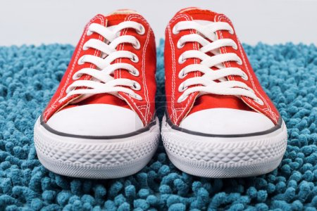 Photo for Trendy red Converse sneakers popular on a blue background - Royalty Free Image