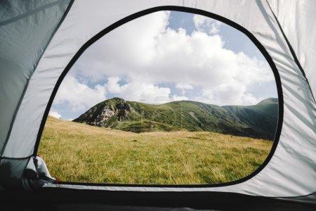 Photo pour Regarder hors de la tente dans les montagnes. tente extérieure et collines. L'Angleterre ou les Alpes - image libre de droit