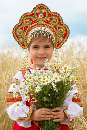 Photo for Girl in the Russian national sundress and a kokoshnik to stand in the field with a bouquet of camomiles - Royalty Free Image