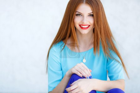 Portrait of beautiful girl with red hair against a light background