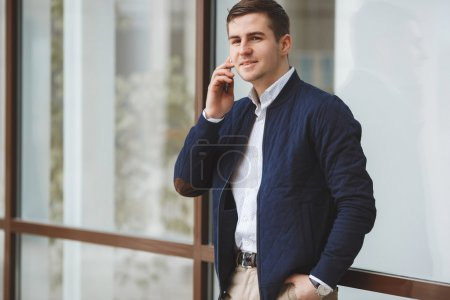 Young businessman talking on cellphone outdoors.