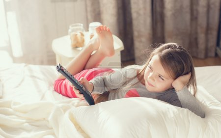 Little girl lying in bed with a remote control TV