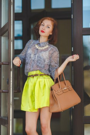 Photo for The beautiful woman with a nutbrown hair and a stylish hairdress, gray eyes and the red lipstick dressed in a skirt of lemon color and a gray blouse wears a white necklace, red nail varnish, poses with a brown bag at an entrance to a supermarket - Royalty Free Image