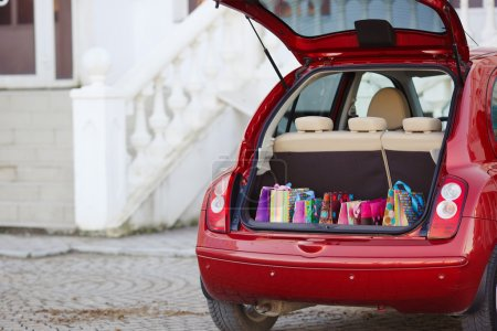 Open the trunk of the car with bags of purchases.