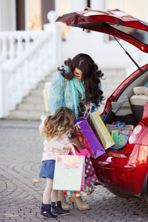 A woman with a child after shopping load the car