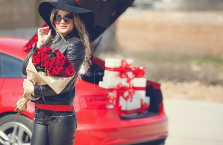 Stylish blonde with a bouquet of red roses near the car