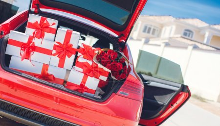 Gift boxes in a luggage carrier of the red car
